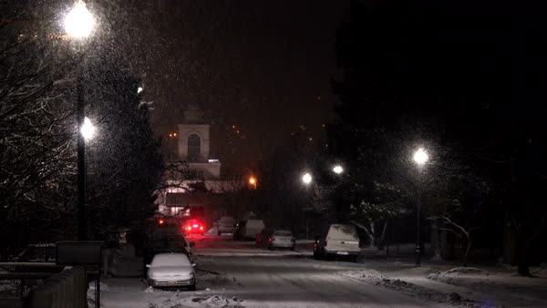 View looking down street as snow is falling at night glowing from the lamp posts. Royalty-free stock video