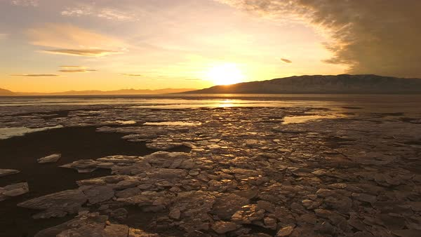 Flying over ice chunks on shoreline of frozen Utah Lake during colorful sunset. Royalty-free stock video