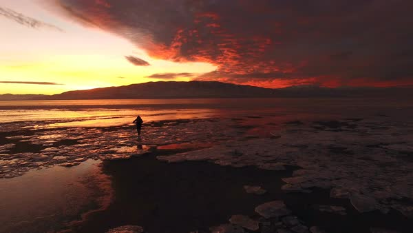View of person walking over ice on edge of lake during colorful sunset in Utah. Royalty-free stock video