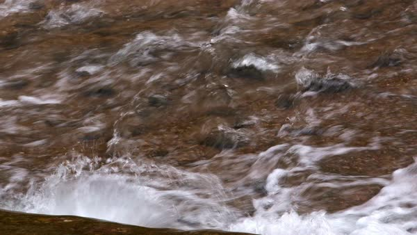 Zoomed view of water hitting rocks as it flows down stream. Royalty-free stock video