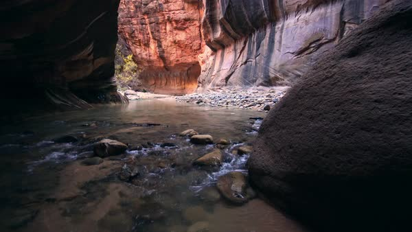 Water flowing through slot canyon as cliff is glowing in the Narrows of Zion National Park Royalty-free stock video