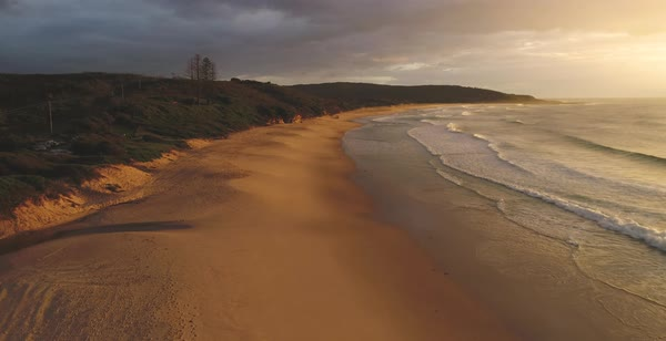 Catherine Hill Bay aerial view of gentle waves washing onto vacant sandy beach with cloudy sky Royalty-free stock video