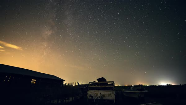 Night scape time lapse panning through the sky viewing stars and tilting up as clouds move by. Royalty-free stock video
