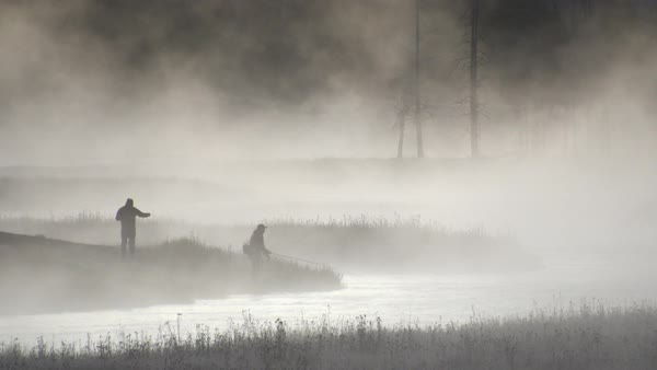 Fly fishermen fishing as fog rises from river Royalty-free stock video