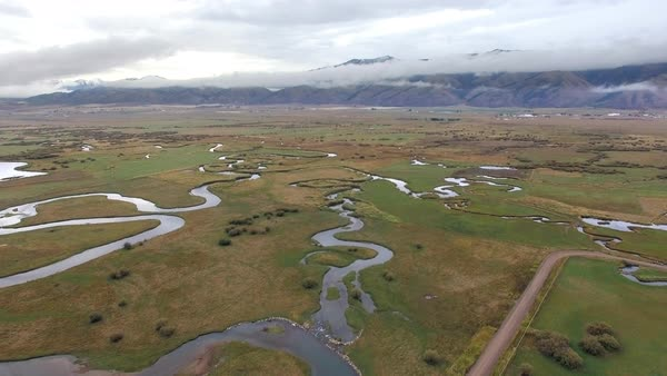Aerial view flying over winding river flowing through the landscape in Wyoming. Royalty-free stock video