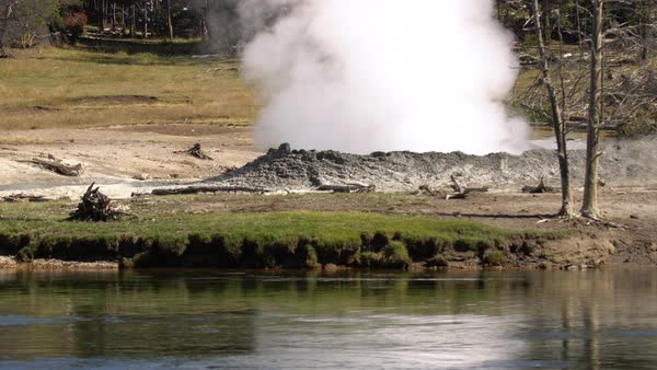 Steam rising from ground next to river in Yellowstone. Royalty-free stock video