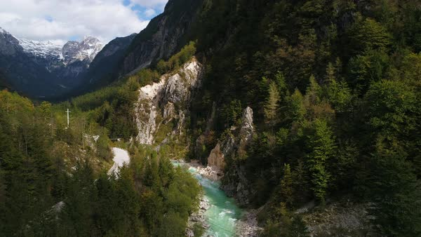 Aerial view of the Soca River flowing out from steep canyon flying backwards downstream to get a wider view of the thick forest. Royalty-free stock video