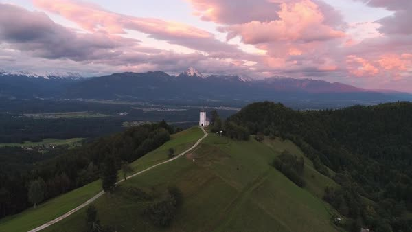 Colorful aerial view of the Jamnik Church on a hilltop at sunset while flying backwards and zooming into the landscape. Royalty-free stock video