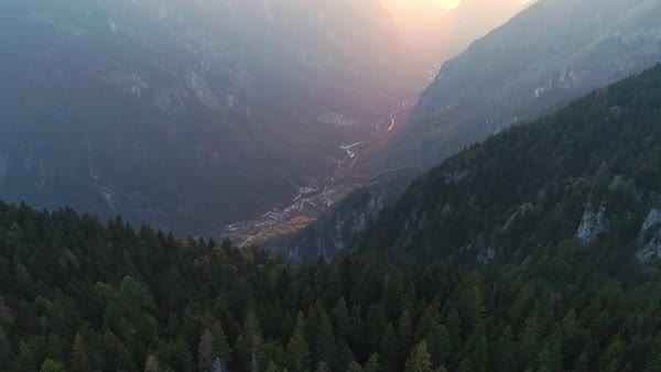 Aerial view flying over forest at dawn towards foggy canyon lit up by the sun in Italy. Royalty-free stock video