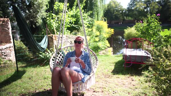 Handheld shot of woman enjoying her coffee in a swing chair Royalty-free stock video