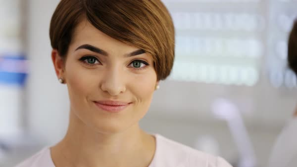 Romantic girl in stylish white shirt with short brunette hair and delicate makeup smiling, looking at camera while posing against white studio wall Royalty-free stock video