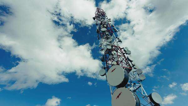 Tall communication tower with blue sky and clouds in the background Royalty-free stock video