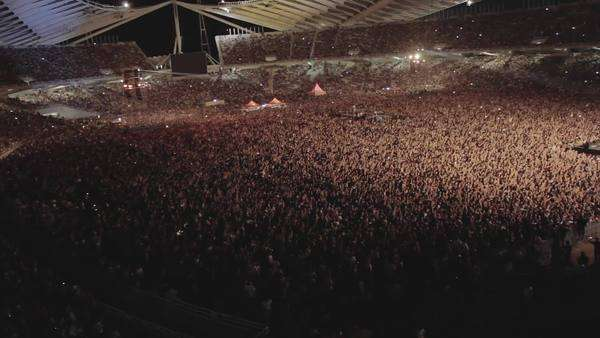 One of the biggest and massive crowds at a live outdoors rock concert in Athens, Greece at the Olympics stadium. High angle aerial view of thousands of people near the stage cheering lifting their hands up in the air. Royalty-free stock video