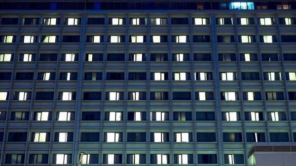 Big city hospital building day-to-night timelapse, rooms, patients. Room lights blinking and patient activity from the outside. Royalty-free stock video