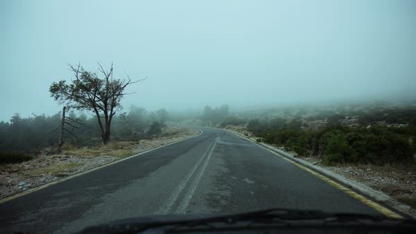 Pov driving on an asphalt countryside mountain road surrounded in mist and fog at winter. Royalty-free stock video