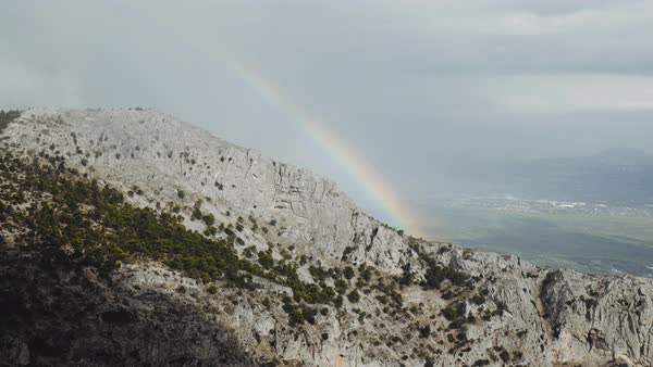 A rainbow appearing on the edge of a cliff,while a dark cloud above is slowly approaching casting its shadow on the mountain Royalty-free stock video