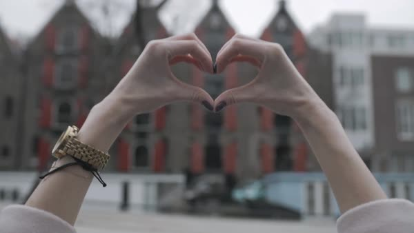 Hand-held shot of a woman forming a heart shape with her fingers Royalty-free stock video