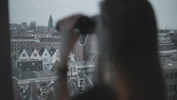 Hand-held shot of a woman using binoculars to look at the city Royalty-free stock video