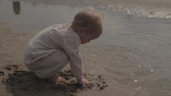Hand-held shot of a toddler throwing wet sand into water on a beach Royalty-free stock video