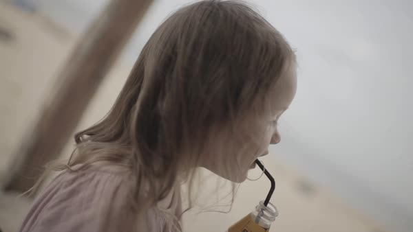 Hand-held shot of a girl drinking from a bottle with a straw Royalty-free stock video