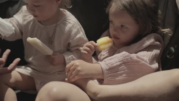Hand-held shot of children eating ice pops on a sofa Royalty-free stock video