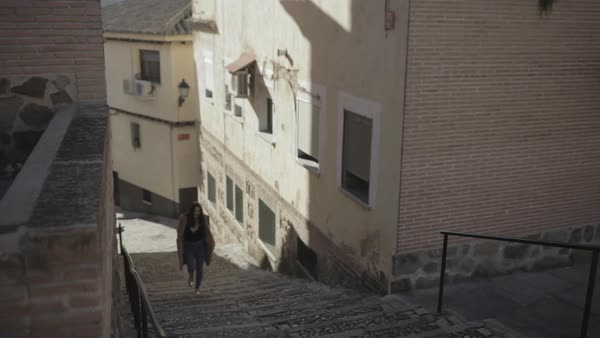 A young woman walking on steps of a Mediterranean town Royalty-free stock video