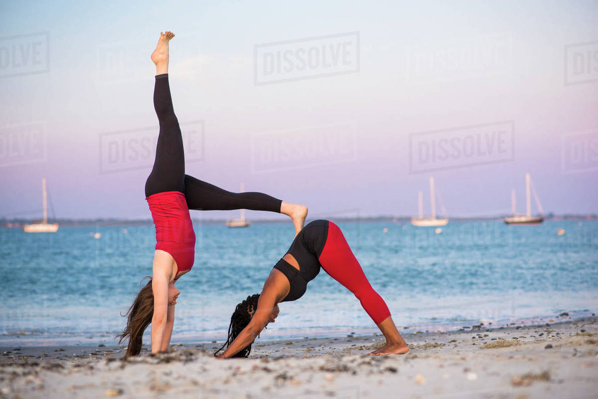 Two women doing yoga in Downward Facing Dog Pose (Adho D49_49_49