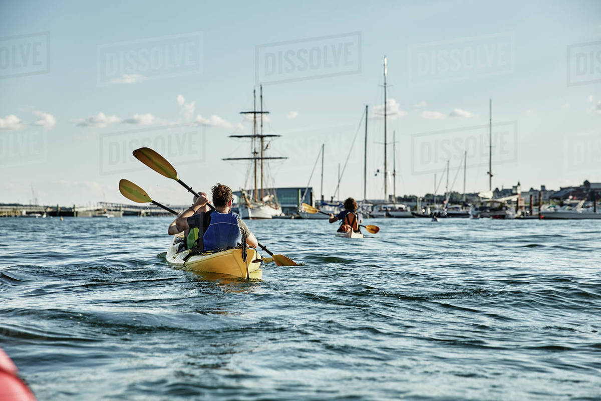 Rear View Of Two Men Paddling In Tandem Sea Kayak Casco Bay Portland Maine USA