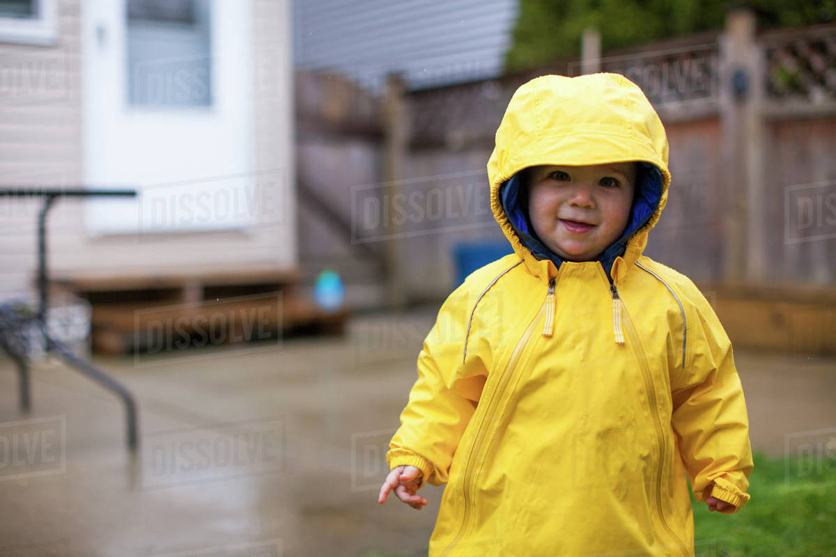 51c8e7d7b Portrait of smiling baby in yellow rain suit