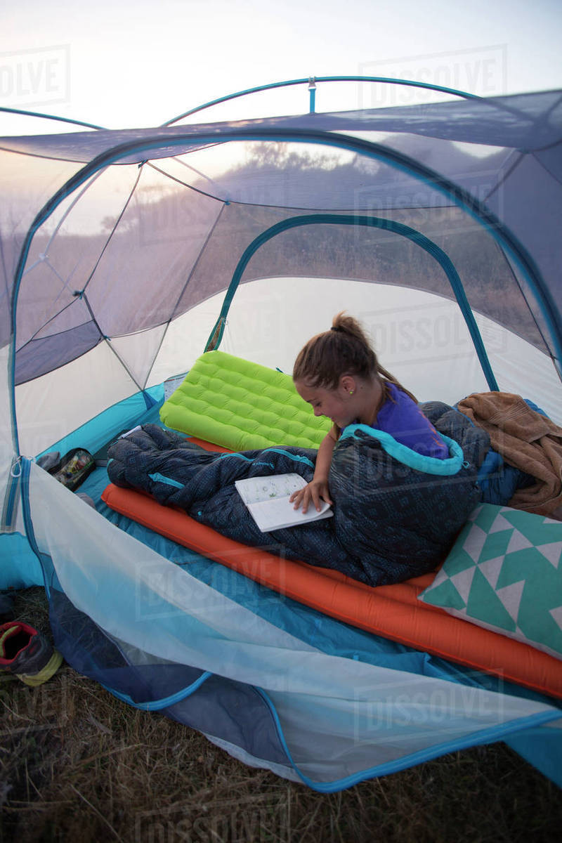 Girl reading journal while lying in sleeping bag inside pitched tent California USA & Girl reading journal while lying in sleeping bag inside pitched tent ...
