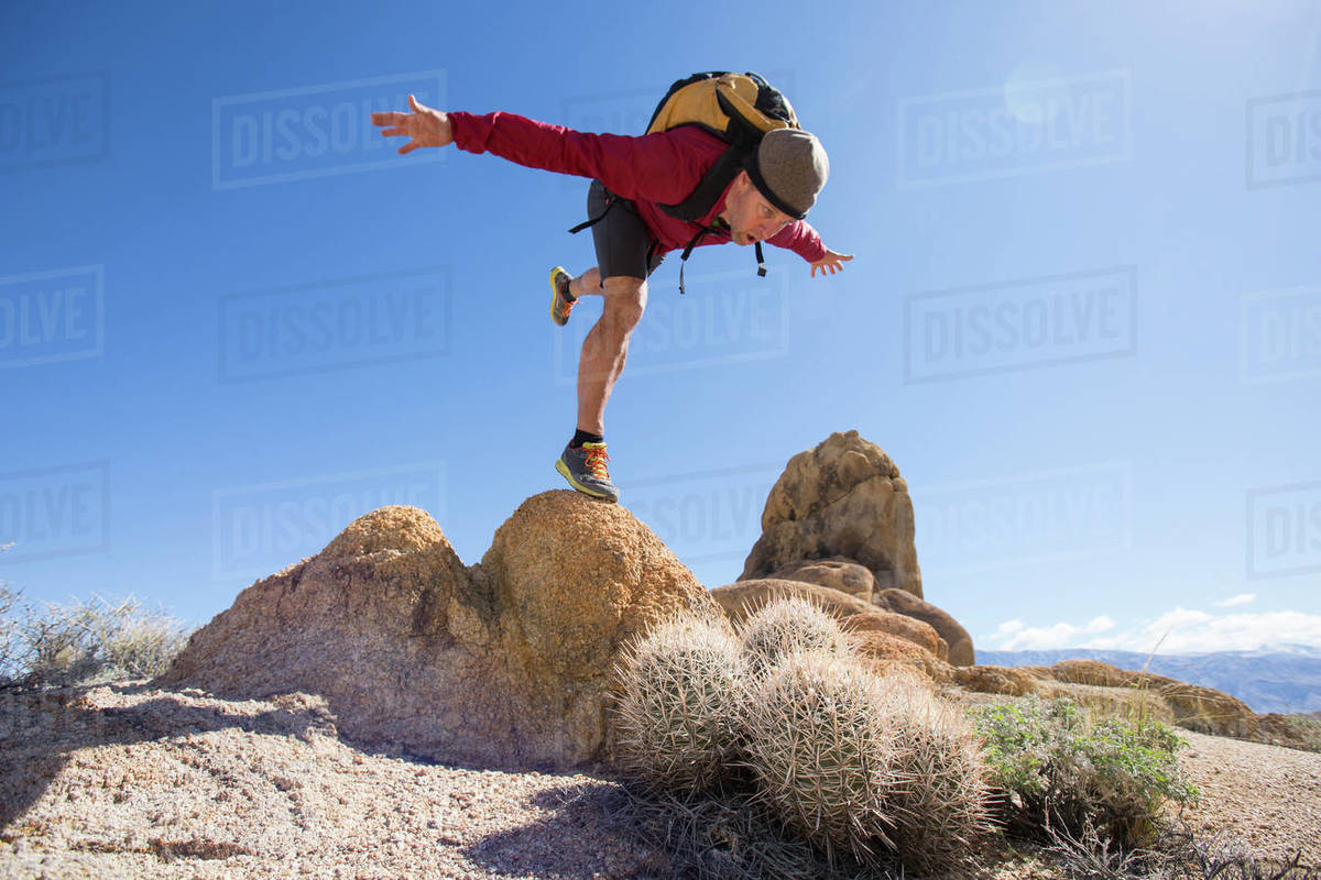 Male Hiker Balancing On One Leg On Top Of Rocks And Pretending To