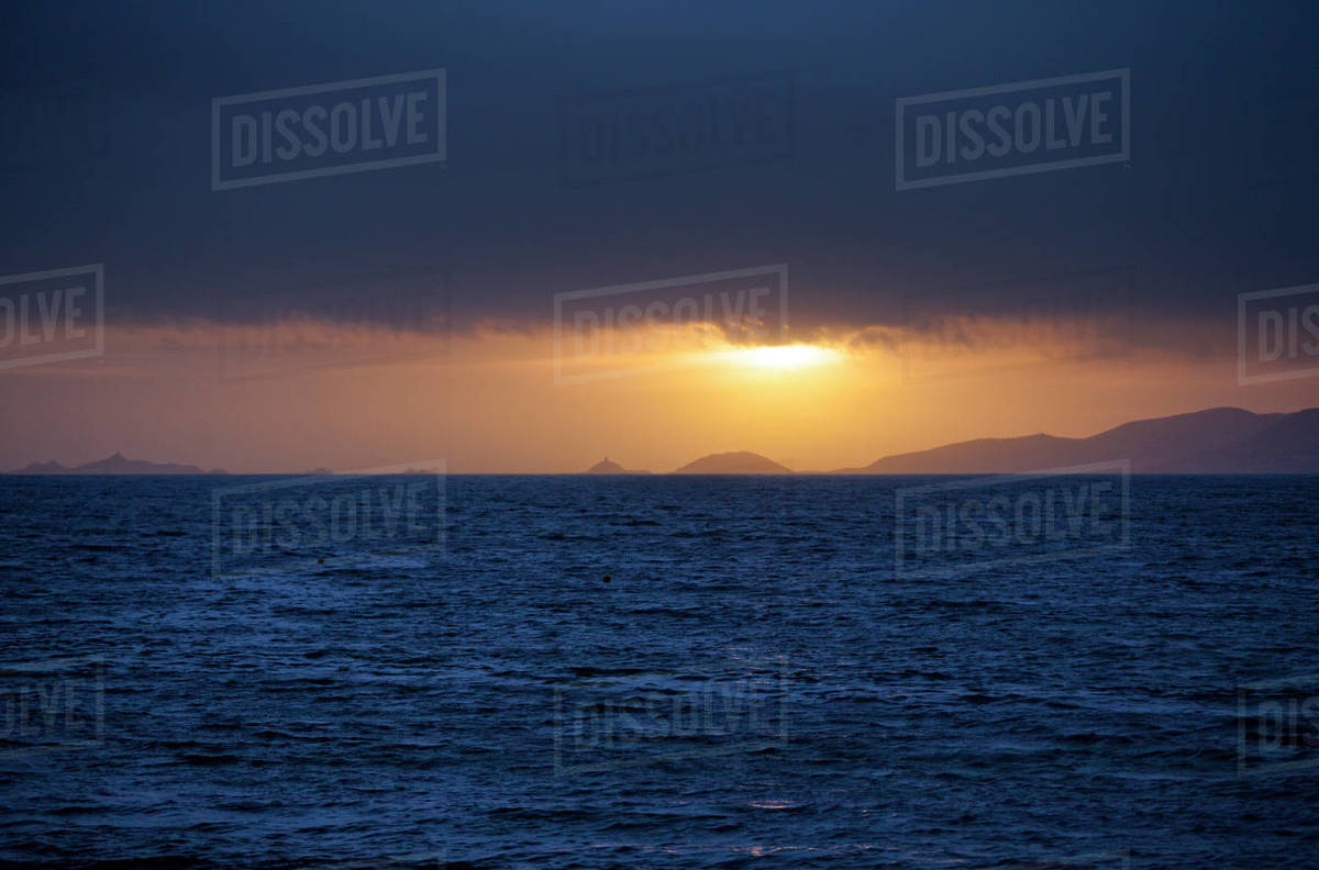 5c0c2a49aae4 Sea at cloudy sunset with silhouettes of coastal hills in background ...