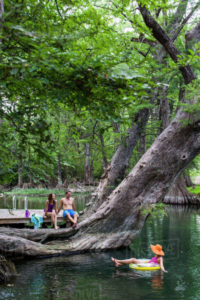 The Blue Hole in Wimberley, Texas is a popular destination for tourists and locals on hot summer days. The clear, cool water flows through cypress trees and offers a refuge from the Texas heat. Royalty-free stock photo