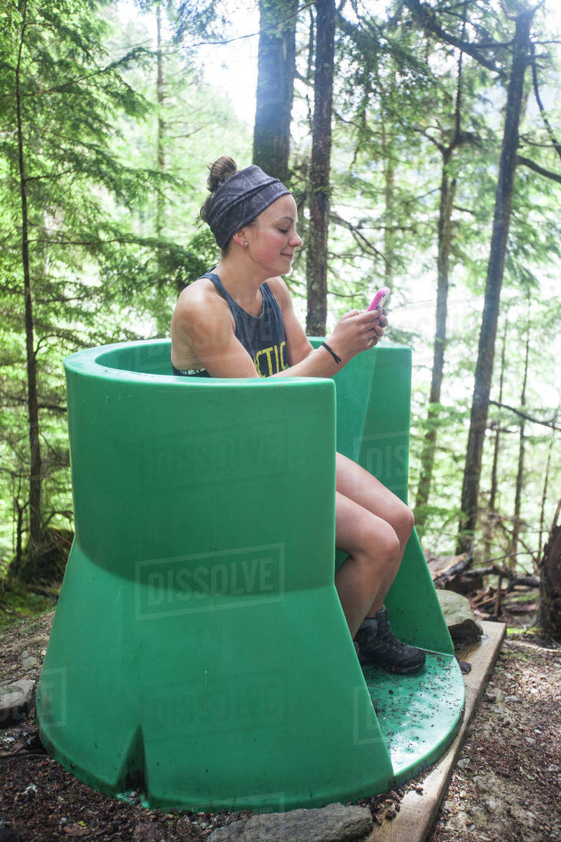 A Young Woman Checks Her Phone While Using An Open Air Outhouse Located In The Forest -2320