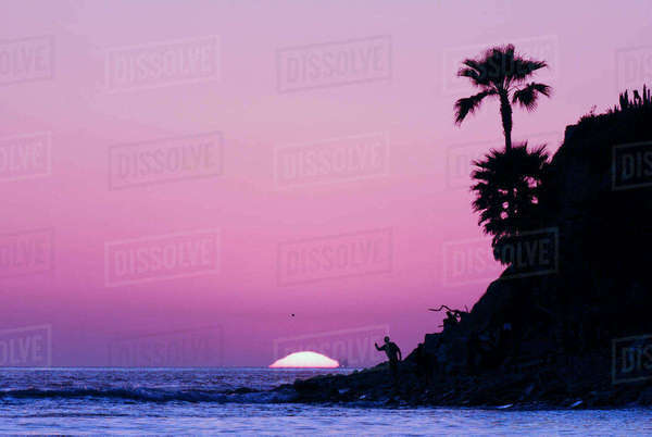 A Person Throwing Rocks Into The Ocean During Sunset In San Diego Royalty-free stock photo