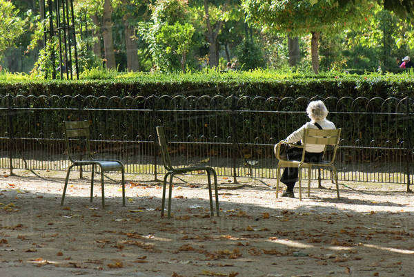 France, Paris, woman sitting alone in park, rear view Royalty-free stock photo