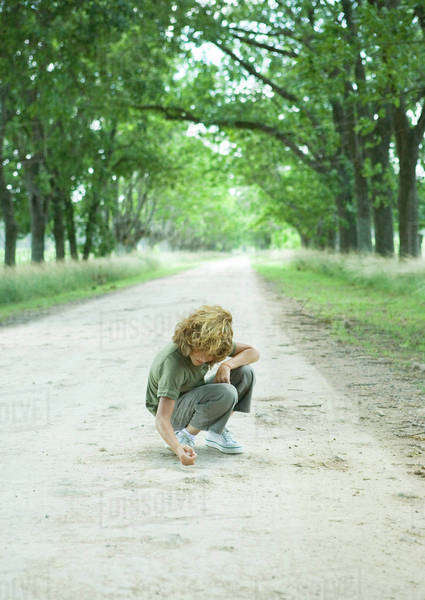 Boy crouching in middle of dirt road Royalty-free stock photo