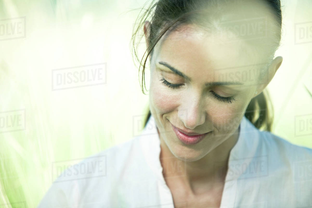 Woman in field, looking down, portrait Royalty-free stock photo