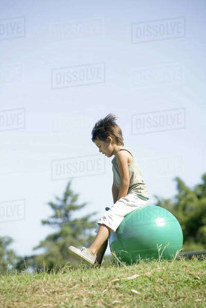 Little boy outdoors sitting on ball, full length Royalty-free stock photo