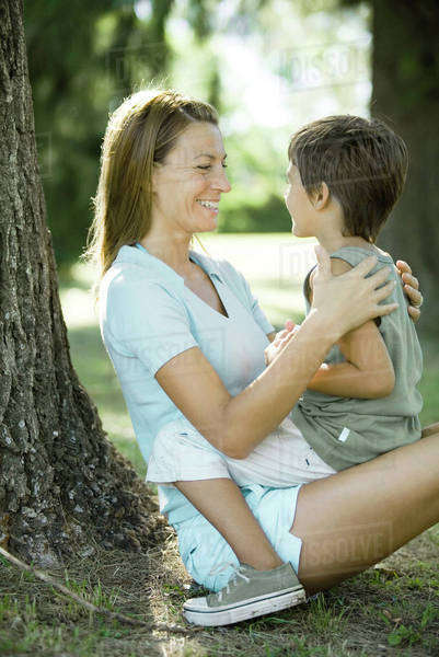 Mother and son outdoors, boy sitting on woman's lap Royalty-free stock photo