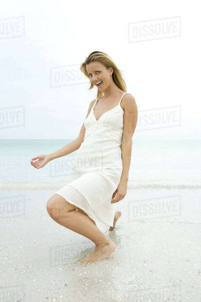 Young woman in sundress crouching in surf, making face at camera Royalty-free stock photo
