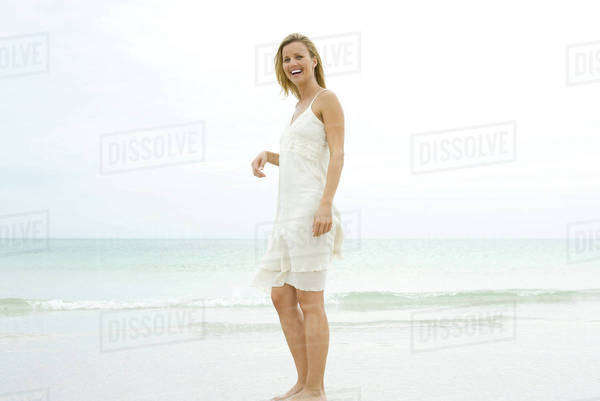 Young woman standing on beach in sundress, laughing Royalty-free stock photo