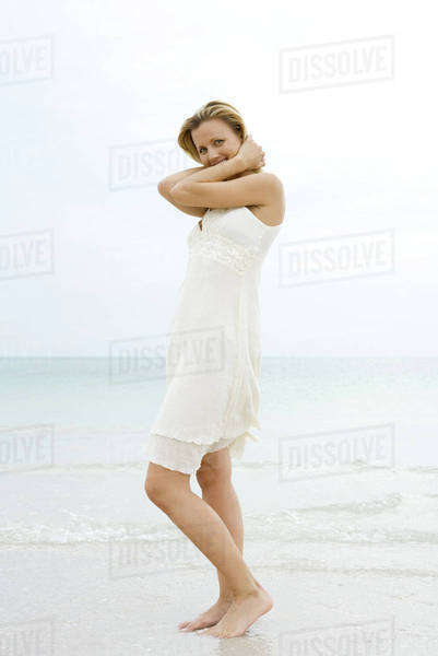 Woman in sundress standing at the beach, holding head, side view Royalty-free stock photo