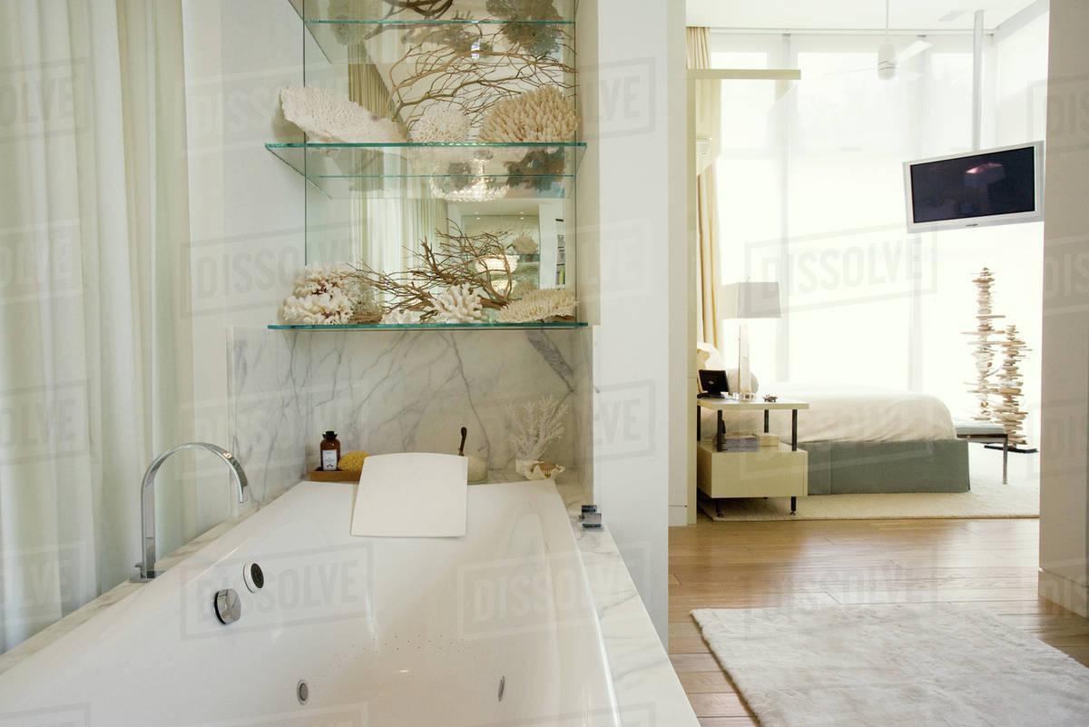 Luxury Hotel Bathroom With Large Bathtub Bedroom In Background