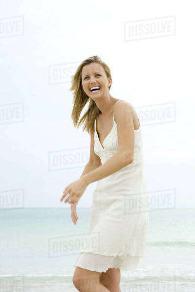 Woman in sundress at the beach, smiling, laughing Royalty-free stock photo