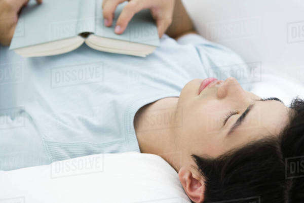 Young male lying on back with eyes closed, holding book on chest Royalty-free stock photo