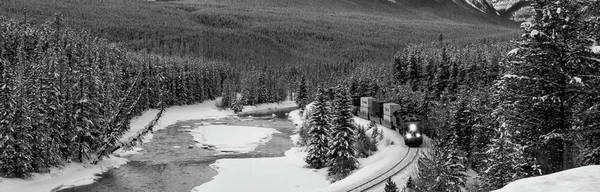 Freight train traveling through a mountain valley in winter in black and white Royalty-free stock photo