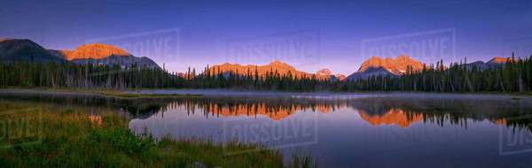 Panoramic shot of mountain peaks and calm waters at sunrise by Buller Pond, Kananaskis Country, Alberta, Canada. Royalty-free stock photo