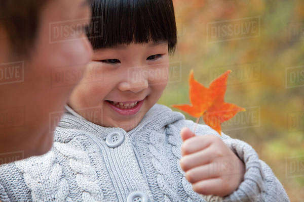 Little girl looking at leaf with her father, close-up, autumn Royalty-free stock photo