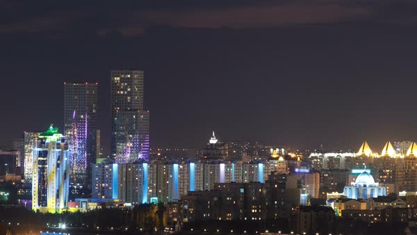 Elevated night view over the city center and central business district with towers. Timelapse from rooftop, illumination turn on, Kazakhstan, Astana, Central Asia Royalty-free stock video